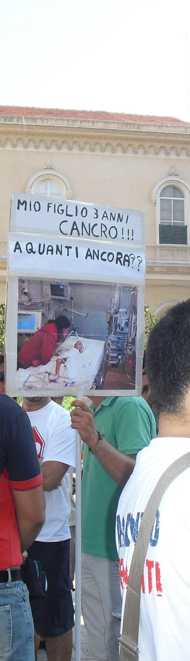 Un bambino ammalato di cancro, ricordato dal cartello portato in Piazza Maria Immacolata da suo padre, alla manifestazione del 17 agosto 2012